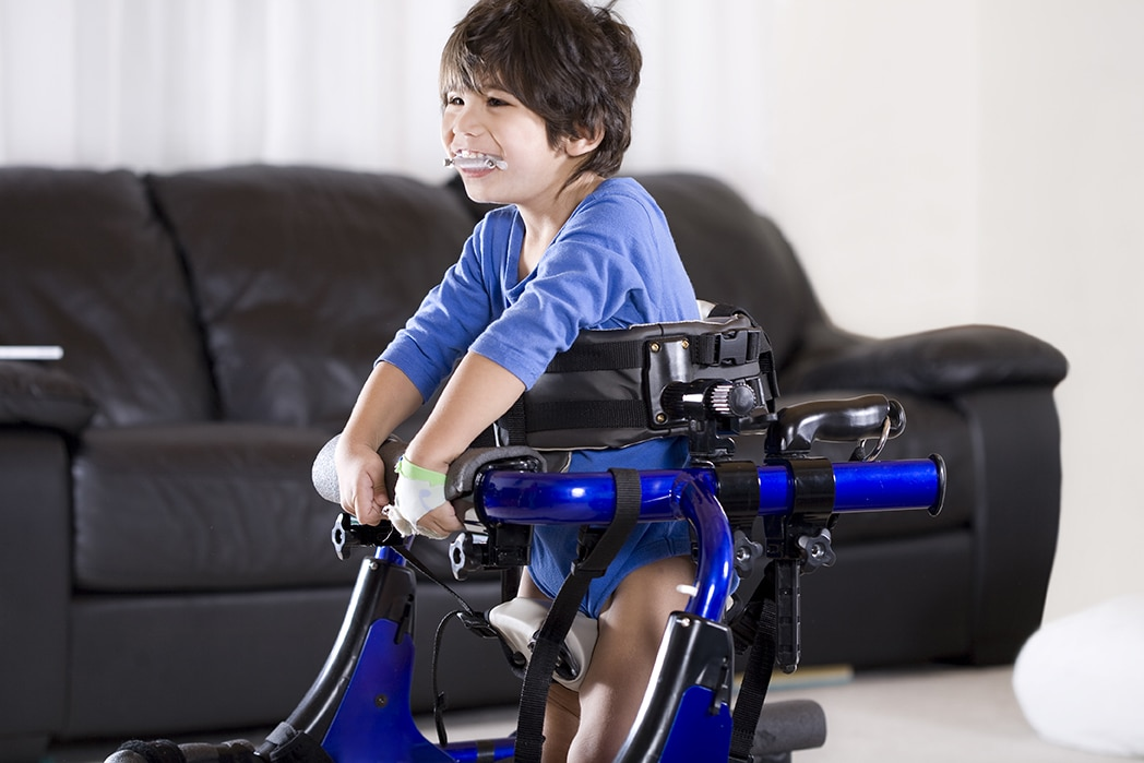 Happy disabled child standing up in his walker